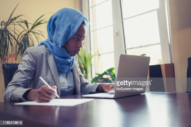 muslim female businesswoman working in office - authors stock pictures, royalty-free photos & images