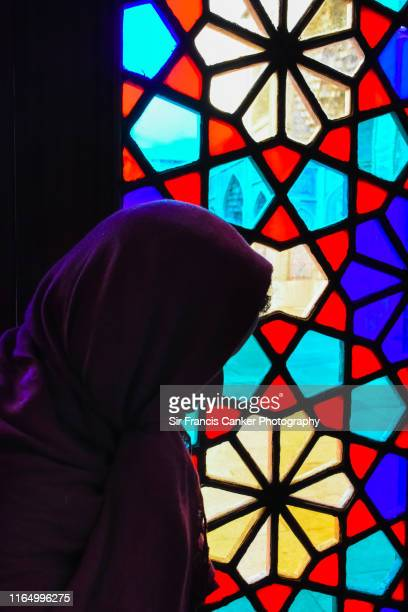 muslim female dressed with a hijab and sadly posing before the stained glass windows of nasir al molk mosque in shiraz, iran - free mosaic patterns stock pictures, royalty-free photos & images