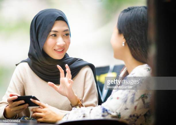 muslim female saleswoman making a pitch to a fellow female using her mobile phone - persuasion stock pictures, royalty-free photos & images