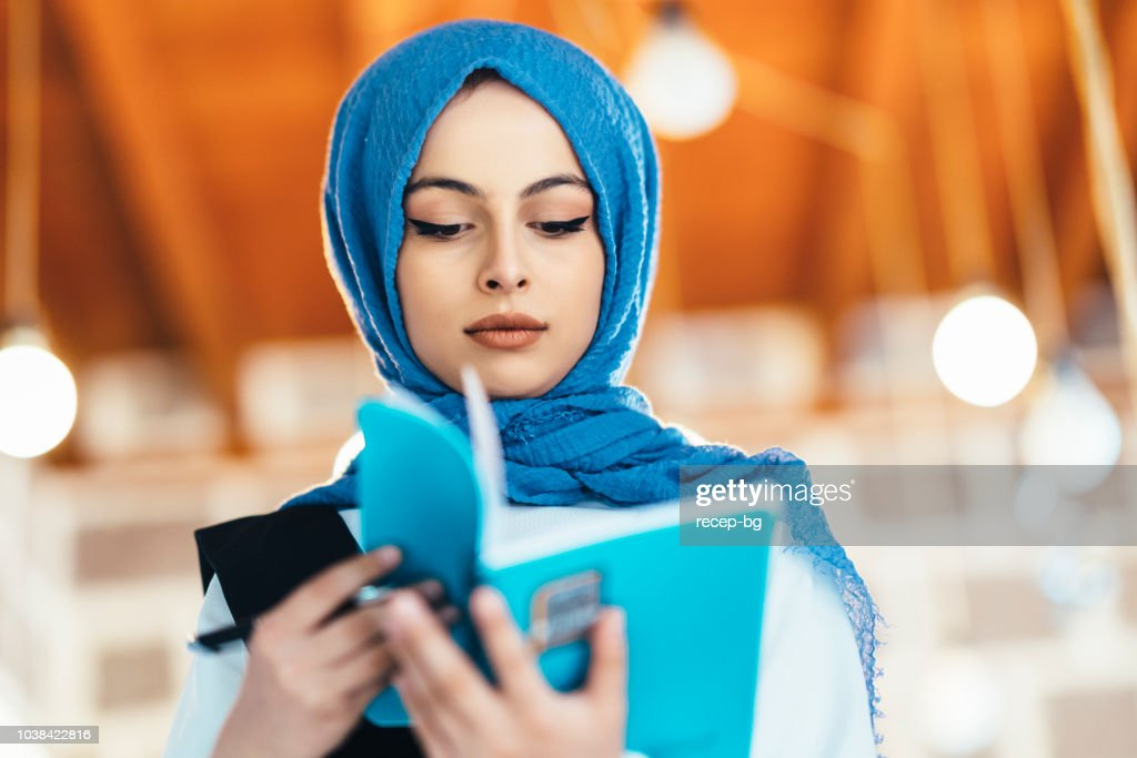 Muslim female student reading book : Stock Photo