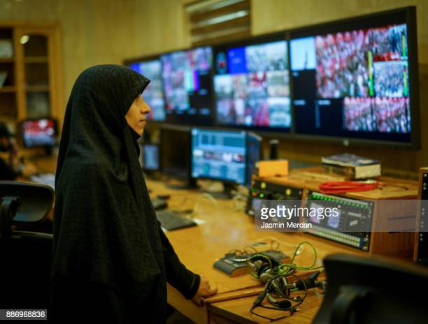 Muslim female TV editor working with vision mixer in television broadcast gallery