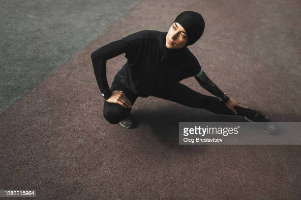 muslim fitness woman in hijab doing stretching exercises outdoors - islam stock pictures, royalty-free photos & images