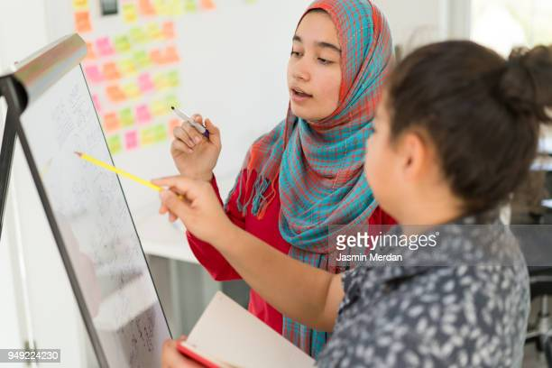 Muslim girl and boy studying at home on whiteboard
