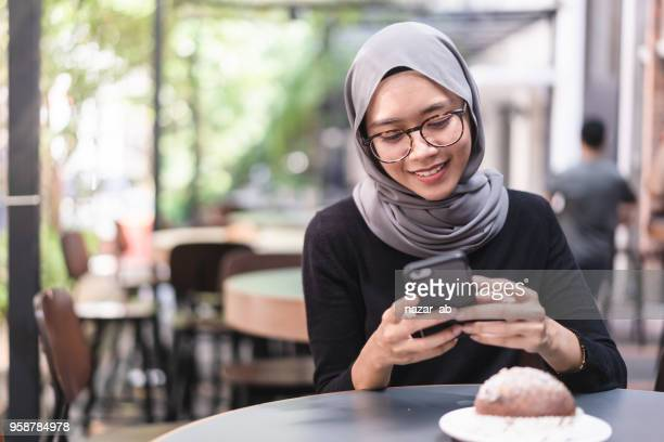 Muslim girl during lunch break checking email.