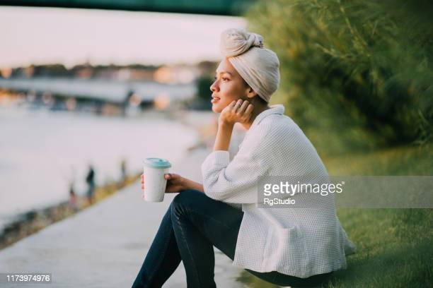 muslim girl enjoying coffee by a river - respect stock pictures, royalty-free photos & images