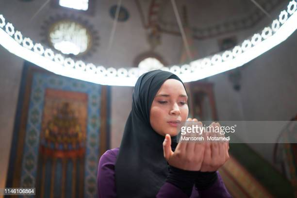 muslim girl is praying in the mosque - muslim praying stock pictures, royalty-free photos & images