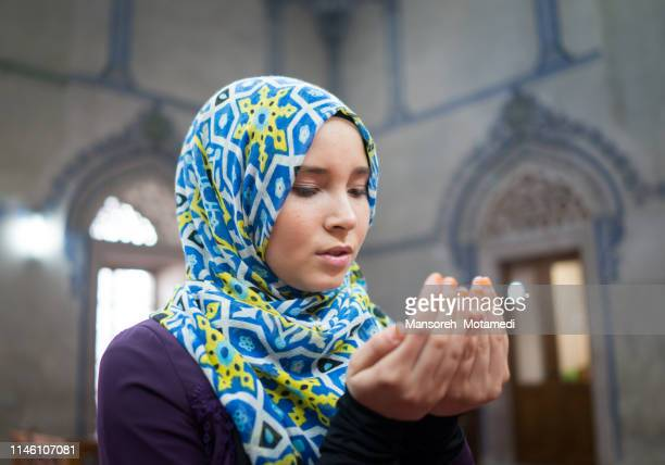 muslim girl is praying in the mosque - religion stock pictures, royalty-free photos & images