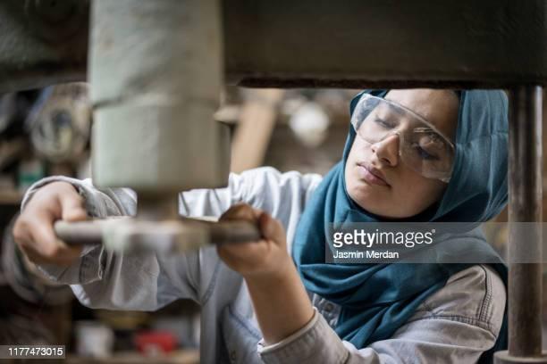 muslim girl is working small family carpenter factory - schutzbrille stock-fotos und bilder