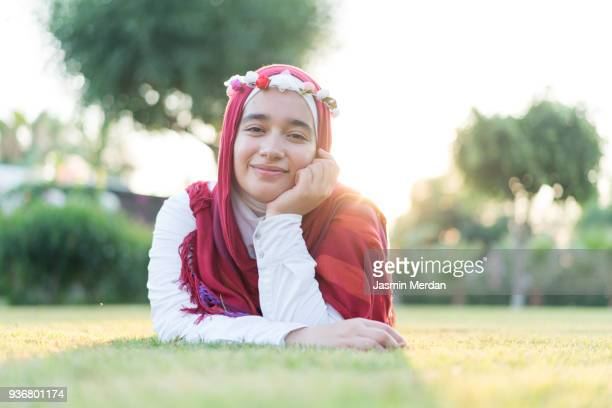 muslim girl on green meadow nearby beach - muslim woman beach stock photos and pictures