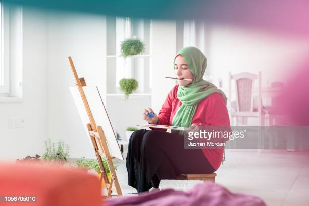 muslim girl painting on easel at home - malerleinwand stock-fotos und bilder
