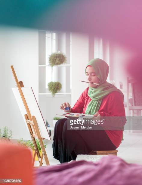 Muslim girl painting on easel at home