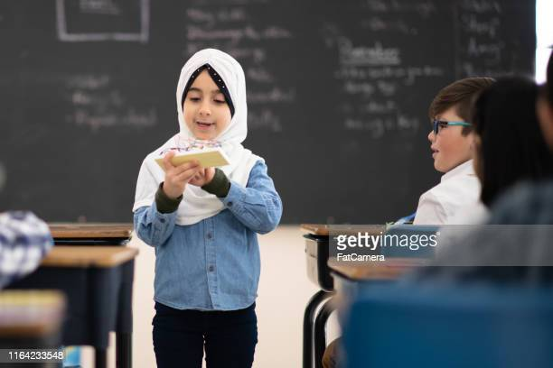 muslim girl presents to her class - headscarf stock pictures, royalty-free photos & images