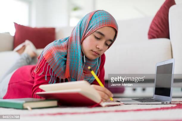 muslim girl studying at home - midden oosterse etniciteit stockfoto's en -beelden