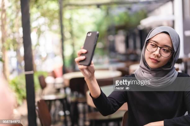 Muslim girl taking selfie.