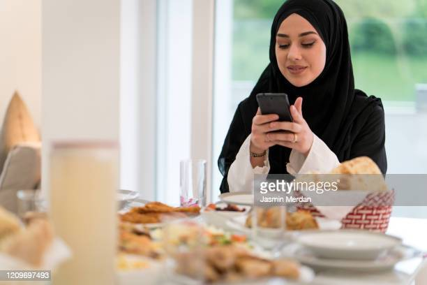 muslim girl with hijab taking photo of lunch table - gulf countries stock pictures, royalty-free photos & images