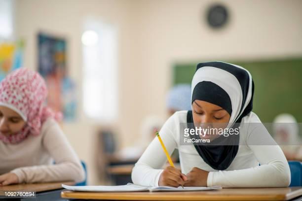 Muslim girl working in class