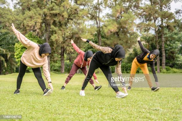 muslim girls exercise stretching in a park - warming up stock pictures, royalty-free photos & images