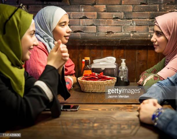muslim girls in restaurant - jordanian workforce stock pictures, royalty-free photos & images