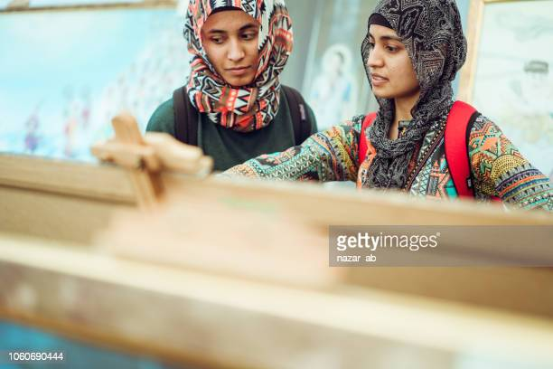 Muslim girls outdoor looking at art in art gallery.
