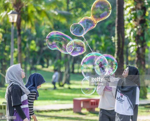 Muslim girls playing with soap bubbles in a park