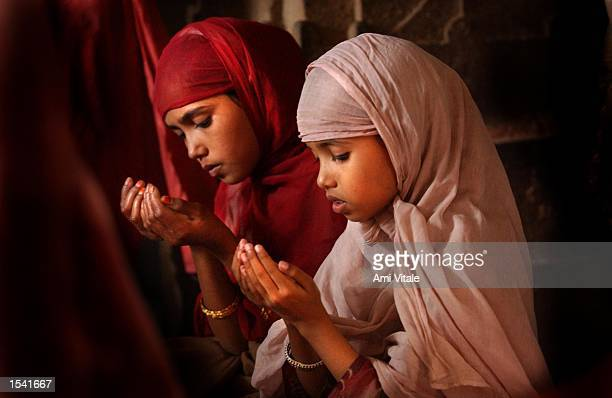 Muslim girls pray May 12 2002 inside a shrine in a refugee camp where over 10000 people are living in the state of Gujarat in Ahmedabad India...