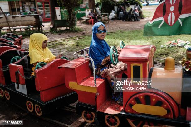 Muslim girls ride on a mini train after attending the Eid Al-Fitr prayer that marks the end of the Holy month of Ramadan at Uhuru Park in Nairobi,...