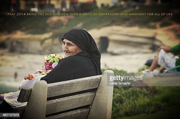 Muslim grandmother and her grand daughter sit on park bench overlooking the ocean in La Jolla, California