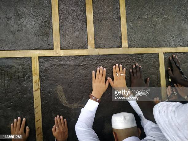Muslim Hajj pilgrims touch the Kaaba stone as they circumambulate the Kaaba at Masjid alHaram in Mecca Saudi Arabia on July 27 2019