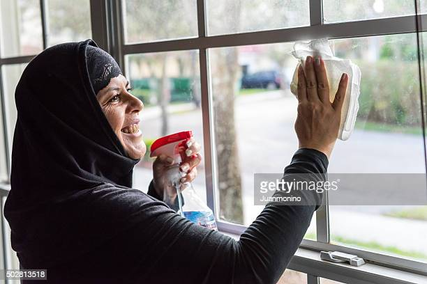 muslim housewife cleaning her home windows - arab women fat stock pictures, royalty-free photos & images