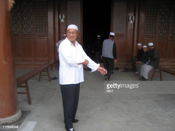 A Muslim Hui religious figure waits for followers to enter a mosque for noon prayers in Tongxin China