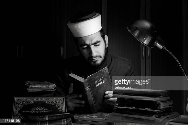 muslim imam reading holy bible on desk in dark - free bible image stock pictures, royalty-free photos & images