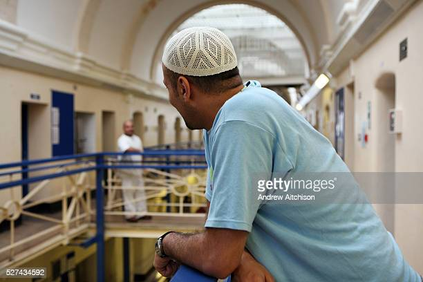 A Muslim inmate on the balcony outside his cell in Wandsworth prison HMP Wandsworth in South West London was built in 1851 and is one of the largest...