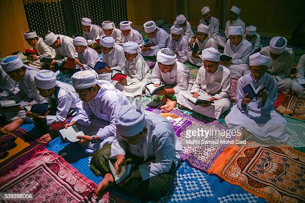 Muslim Islamic students read the Koran inside the Sultan Abdul Samad building during the holy month of Ramadan at Dataran Merdeka on June 11 2016 in...