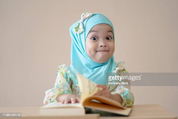 muslim kid doing homework and reading a book. kid enjoy learning with happiness at home. clever,education and smart learning concept. - beautiful ramadan stock pictures, royalty-free photos & images