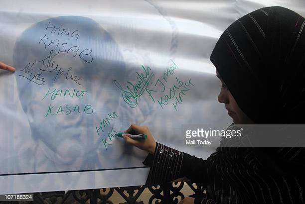 Muslim lady signing on the board demanding to hang on 26/11 terrorist Ajmal Kasab at a memorial outside the Taj Mahal Palace hotel on the second...