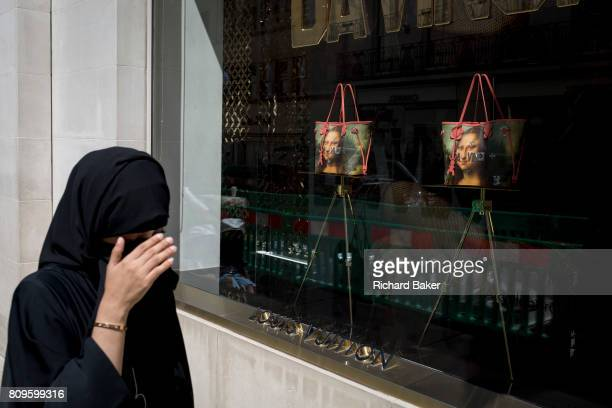 A Muslim lady wearing a Niqab passes the luxury shop window of Louis Vuitton featuring their exclusive range of bags with the face of Leonardo da...