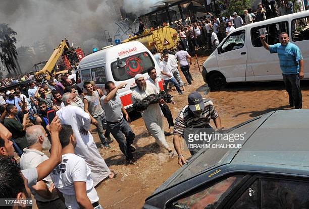 Muslim Lebanese carries the burnt body of a victim of a powerful explosion near altaqwa mosque in the northern Lebanese city of Tripoli on August 23...