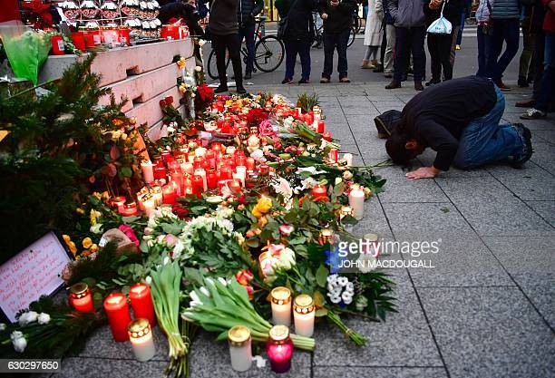 A Muslim mam prays at a makeshift memorial for the attack victims on December 20 2016 in front of the KaiserWilhelmGedaechtniskirche in Berlin where...