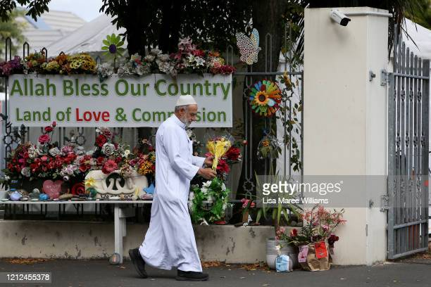 Muslim man adjusts flowers at the entrance of the Masjid An-Nur mosque on March 15, 2020 in Christchurch, New Zealand. 51 people were killed and...