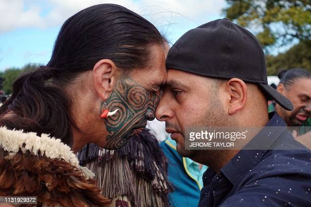 Muslim man and another local perform a traditional Maori 'hongi' greeting, a touching of noses, during a gathering for congregational Friday prayers...