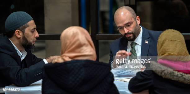Muslim man and his family meet with an immigration attorney during a town hall meeting by the Council on American-Islamic Relations at the Dar...