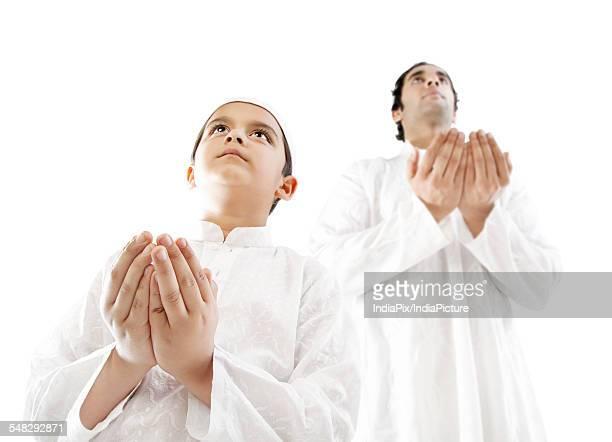 muslim man and his son praying - salah islamic prayer stock pictures, royalty-free photos & images