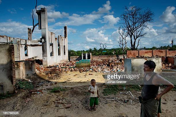 Muslim man and his son walk around on the remains of their home after waves of violence led against Muslims by Buddhists have destroyed and left many...
