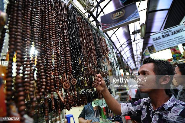 Muslim man buys wooden beads at Ampel traditional market during Ramadan on July 13 2014 in Surabaya Indonesia Ramadan the ninth month of the Islamic...