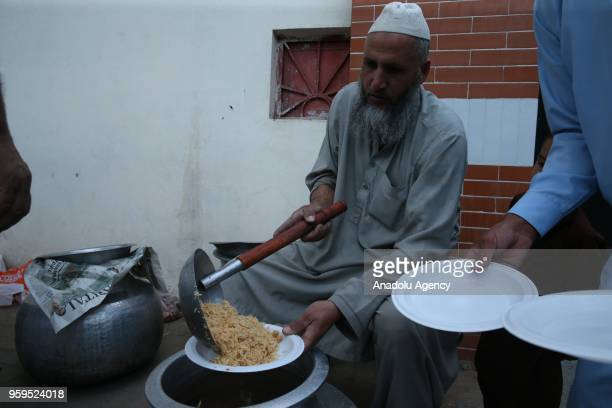 Muslim man fills a plastic plate within the iftar dinner preparations on the first day of holy Islamic month of Ramadan in Islamabad Pakistan on May...