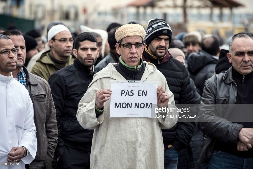 A Muslim man holds a placard, reading 'Not in my name', during a gathering on January 9, 2015 near the mosque of Saint-Etienne, eastern France, after the country's bloodiest attack in half a century on the offices of the weekly satirical Charlie Hebdo killing 12 people on January 7.
