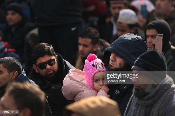 A muslim man holds his daughter as he prays at a prayer and demonstration at JFK airport to protest President Donald Trump's Executive Order banning...