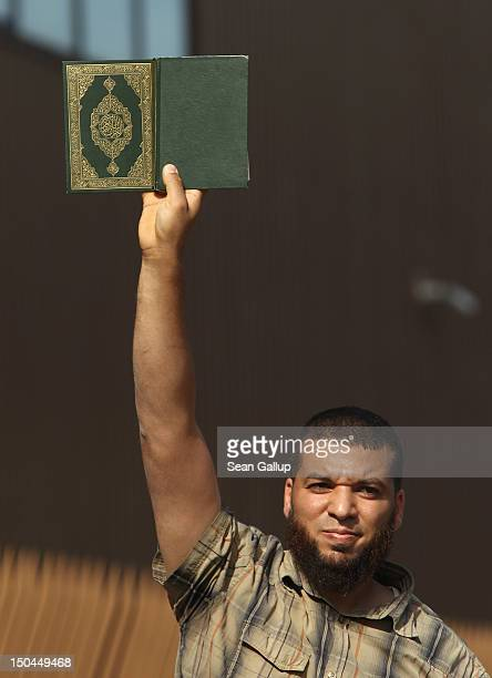 Muslim man holds up a copy of the Koran in response to supporters of the pro Deutschland rightwing antiIslam group displaying a caricature of the...