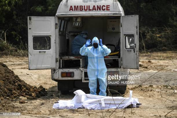 Muslim man in protective gear offers funeral prayers for a Central Reserve Police Force personnel who died from the COVID-19 coronavirus before his...