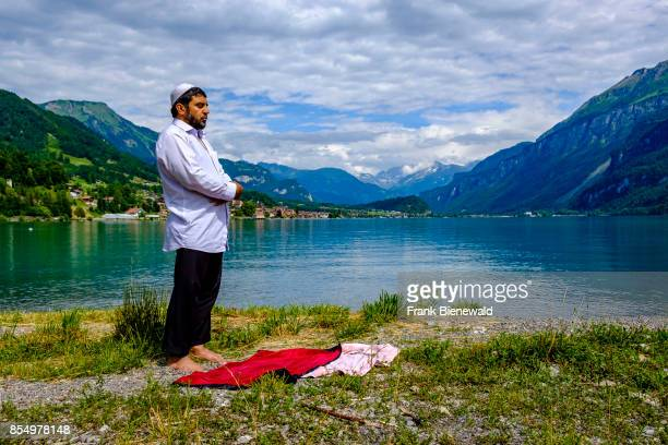 A muslim man is praying at Lake Brienz Brienzer See high mountains in the distance